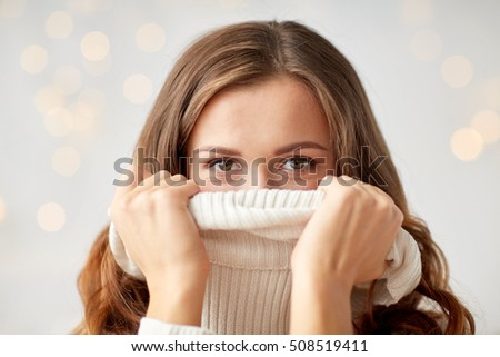 winter, christmas and people concept - young woman or teen girl pulling up pullover collar