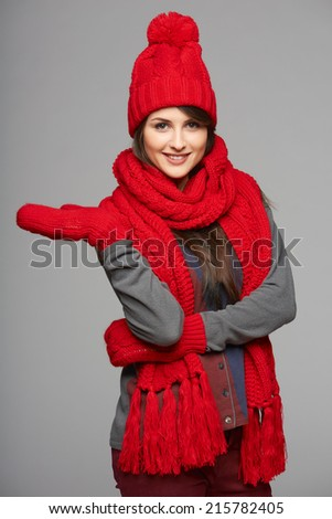Winter, christmas, holidays concept. Smiling beautiful woman in red hat, scarf and mittens showing open hand palm with copy space for product or text, over gray background - stock photo