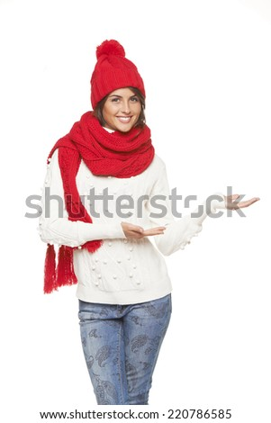 Winter, christmas, holidays concept. Smiling beautiful woman in warm winter red hat and scarf showing open hand palm with copy space for product or text, over white background - stock photo