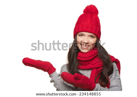 Winter, christmas, holidays concept. Smiling beautiful woman in warm winter red hat and scarf showing blank copy space, over white background