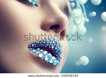 Winter Christmas lips make up with gems. Winter model Woman makeup. Creative Girl Make up. Holiday Make-up with gems on the lips. Snow Queen High Fashion Portrait over Blue Snow Background. Crystals