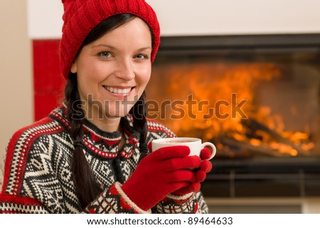 Winter Christmas woman with hat and gloves drink by fireplace - stock photo