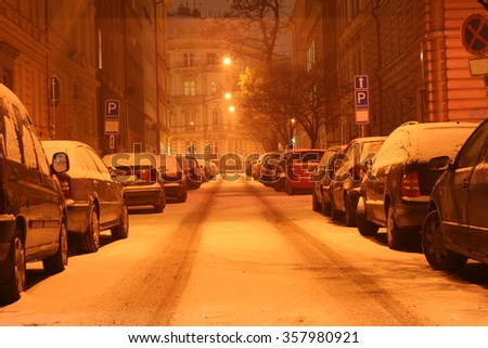 Winter city center street at night with parked cars covered by fresh white snow. New Town, Prague   - stock photo