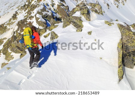 Winter climber carries a backpack and gear on snowy alpine route - stock photo