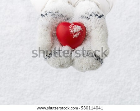 Winter, close up of little girl hands holding red rubber heart with copy space