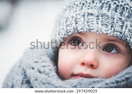 winter close up outdoor portrait of adorable dreamy baby girl in grey knitted hat and scarf - stock photo