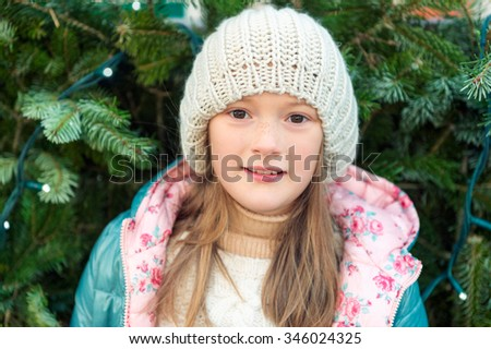 Winter close up portrait of a cute little girl of 8 years old, standing next to Christmas tree, wearing a hat - stock photo