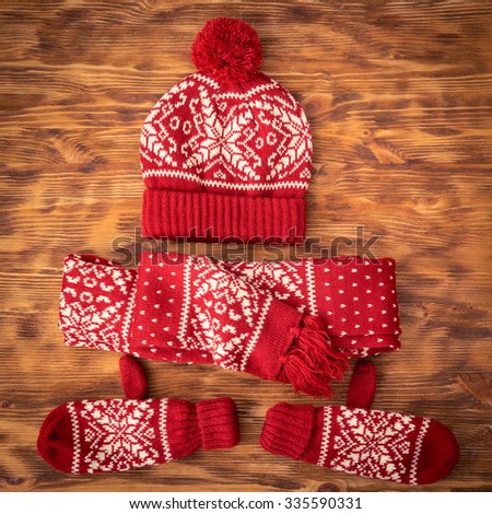 Winter clothes set - woolen hat; scarf and gloves on wood background - stock photo