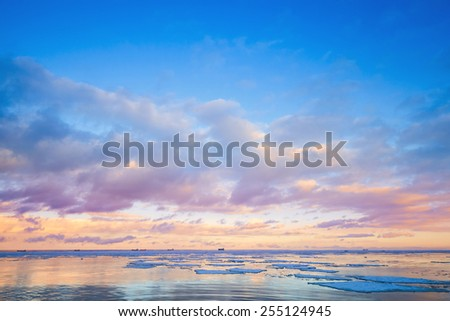 Winter coastal landscape with ice fragments and colorful cloudy sky over horizon. Gulf of Finland, Russia