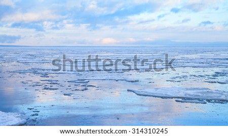 Winter coastal seascape with floating ice fragments on still cold water. Baltic Sea, Gulf of Finland, Russia - stock photo