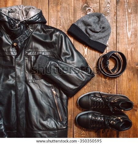 Winter collection of men's clothing in casual style on the wooden background. new men's leather winter jacket, hat, belt and shoes. Square photo - stock photo