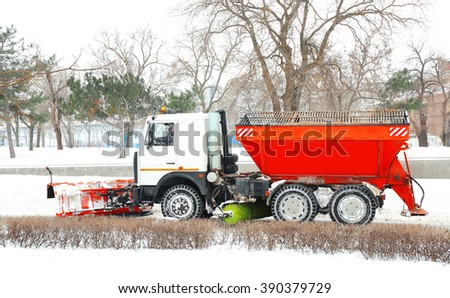 Winter concept. Car for snow removal is cleaning the road - stock photo