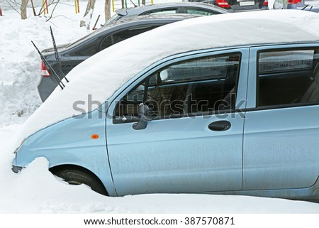 Winter concept. Car is covered with snow, close up