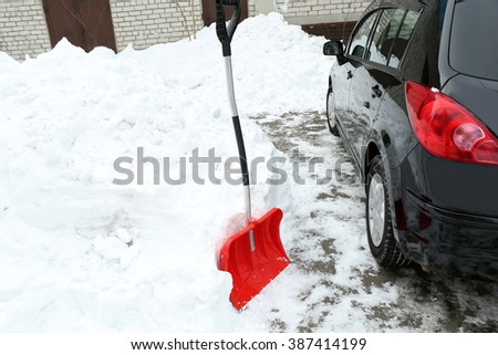 Winter concept. Red shovel for cleaning the driveway of snow - stock photo