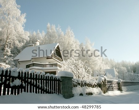 Winter cottage in the mountains surrounded by birches covered with frost. - stock photo