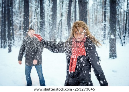 Winter couple having fun playing snowball fight - stock photo