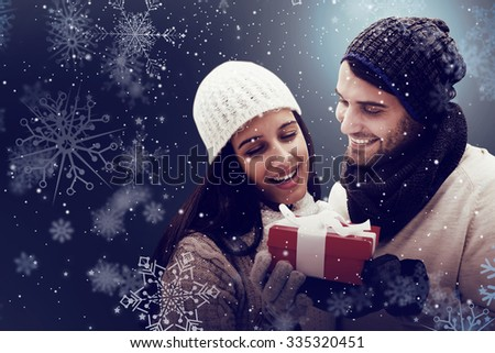 Winter couple holding gift against snow - stock photo