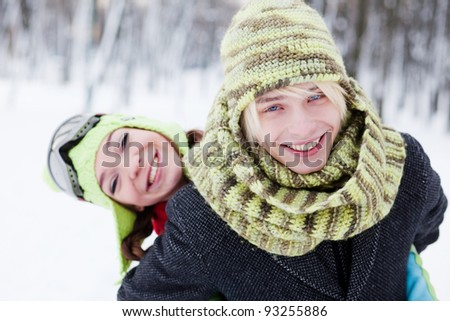 Winter couple  in snow smiling happy. Beautiful young couple