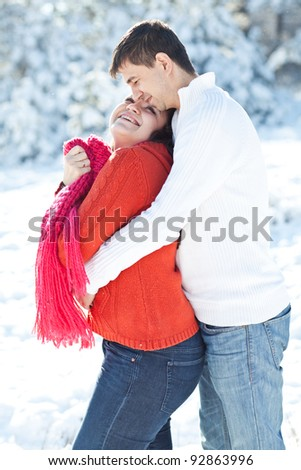 Winter couple piggyback in snow smiling happy and excited. Beautiful young couple