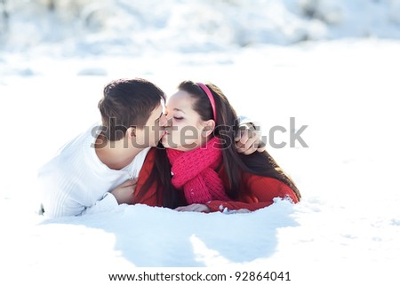 Winter couple piggyback in snow smiling happy and excited. Beautiful young couple - stock photo