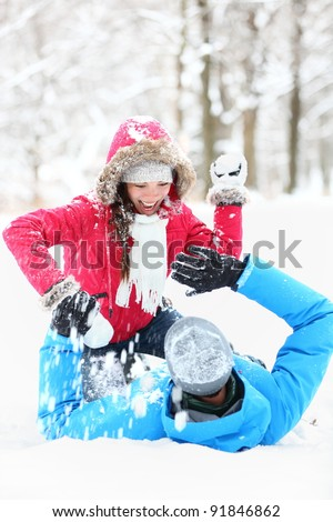 Winter couple snowball fight. Young couple having fun in snow outside. young couple in their twenties.