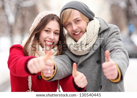 Winter couple with thumbs up - stock photo