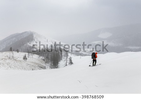 Winter cross country trek through the snowy woods on the track in the mountains