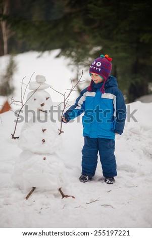 Winter. cute boy making snowman - stock photo