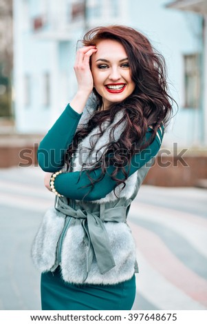 Winter cute girl fashion. Smiling woman wearing sweater fur vest. stylishly dressed beautiful young girl in a fur vest walks at  the street - stock photo