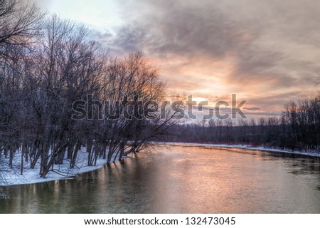 Winter day on snow covered river in Northern Ontario sunrise sky