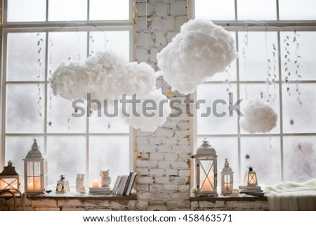 winter decor on windowsill with lanterns and clouds