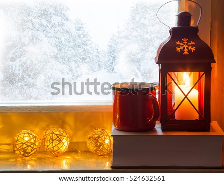 Winter decoration with lantern, hot chocolate cup, book and lights on windowsill