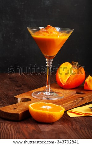 Winter dessert with persimmon on a dark background. Glass of smoothie with persimmon