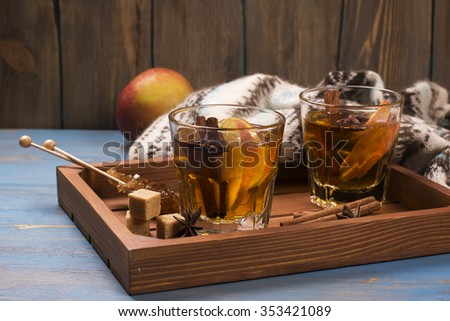 Winter drink. Warm mulled apple cider with spices: cinnamon, cloves, honey, anise stars over wooden tray. Selective focus. Toned image - stock photo