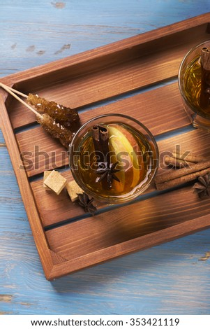 Winter drink. Warm mulled apple cider with spices: cinnamon, cloves, honey, anise stars over wooden tray. Top view. Selective focus. Toned image - stock photo