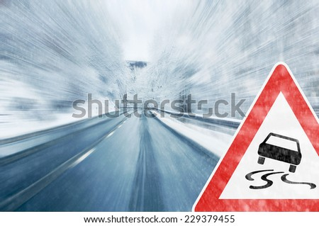 Winter Driving - Caution - Mountain road with snowfall and traffic sign - stock photo