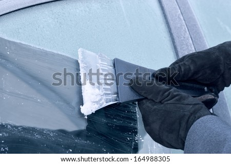 winter driving - scraping ice from a windshield - stock photo