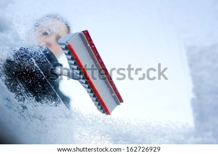 winter driving - scraping ice from a windshield Photo has been taken from the inside of the car.  - stock photo