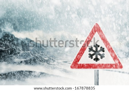 winter driving - snowfall in the mountains - risk of snow and ice - warning sign  - stock photo