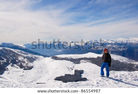 Winter entertainment/Smiling female snowboarder standing on snow with mountains in the background - stock photo