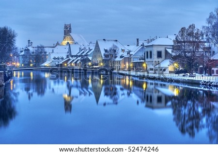 Winter evening in the snow covered old german town near Munich on the river Isar - stock photo