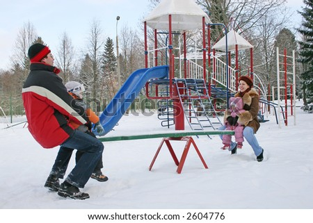 winter family on seesaw - stock photo
