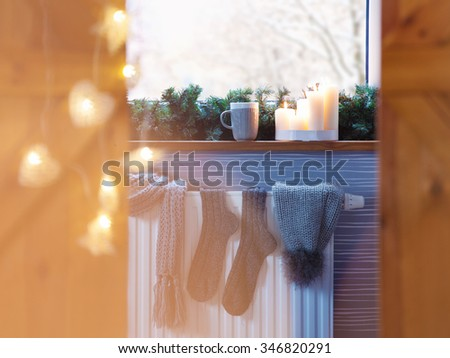 Winter fashion accessories hat socks drying on a heater, christmas lights,  snow window view and hot drink - stock photo