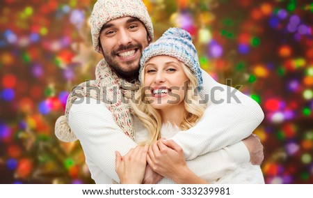 winter, fashion, couple, christmas and people concept - smiling man and woman in hats and scarf hugging over holidays lights background - stock photo