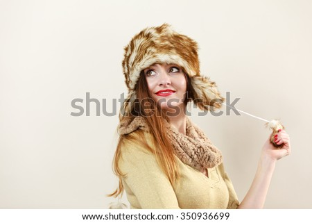 Winter fashion. Happy young woman wearing fashionable wintertime clothes fur cap portrait