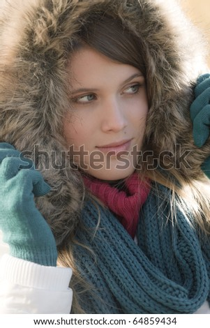 Winter fashion - woman with fur hood and gloves outside, desaturated colors