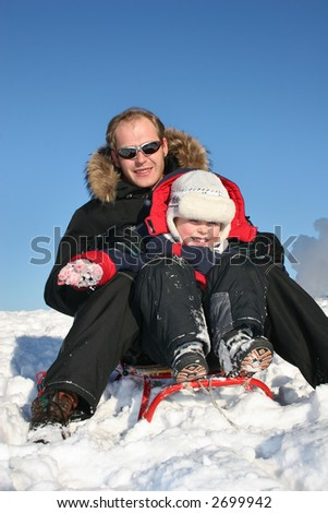 winter father with child on sled