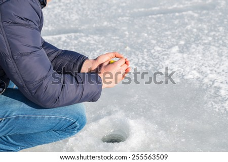 Winter fishing. Ice fishing. Fisherman on ice fishing from the well, a special winter fishing rod. Fishing in winter. Active, cold, fish, winter fishing tackle. Sport winter fishing. - stock photo