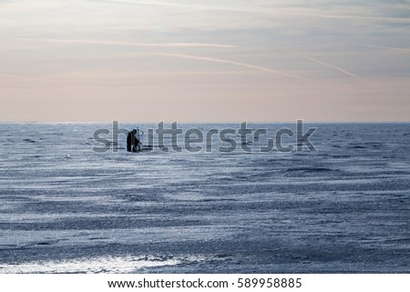 Winter fishing - lone fisherman on the ice.