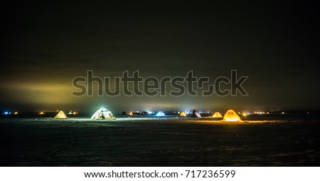 Winter fisherman stock images royalty free images for Ice fishing at night